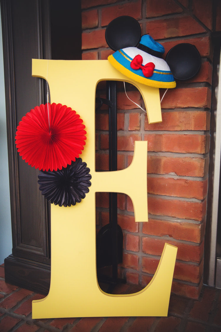 "Closeup photo of yellow wooden ""E"" with paper pinwheels and Donald Duck mouse ears hanging from it"