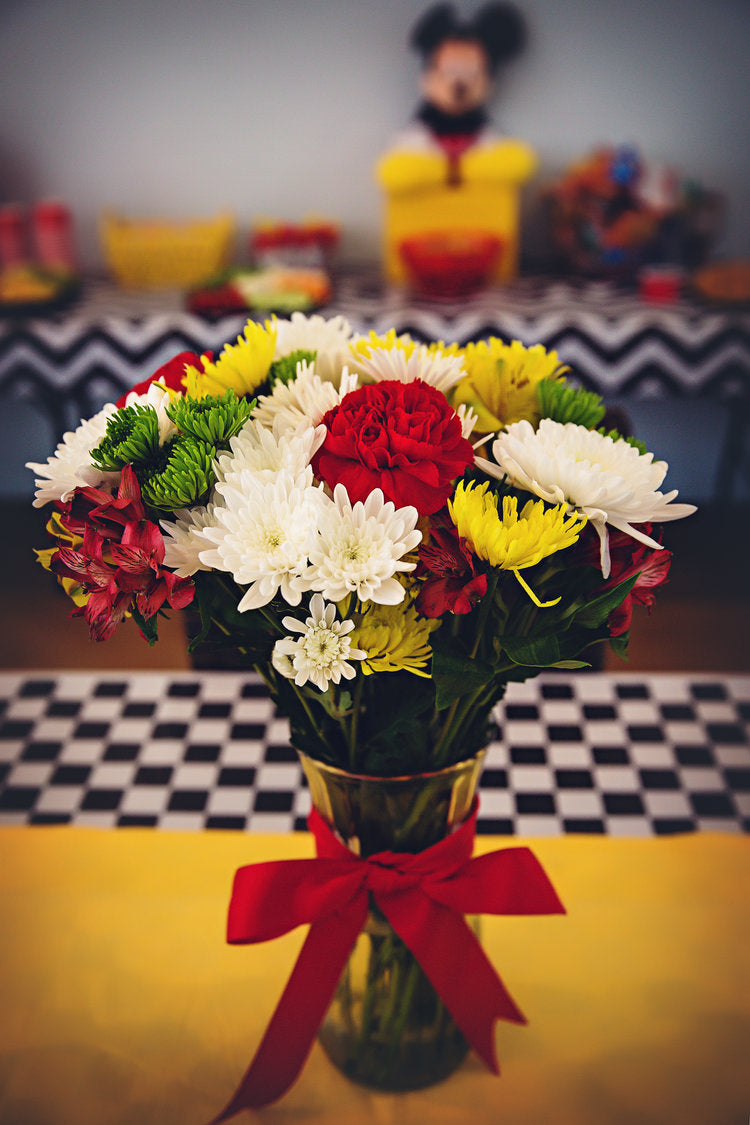 Flower bouquet filled with red, white, yellow, and green flowers in a glass vase