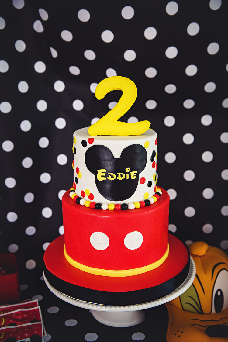 2 tier birthday cake decorated in Mickey Mouse colors of red, white, black, and yellow