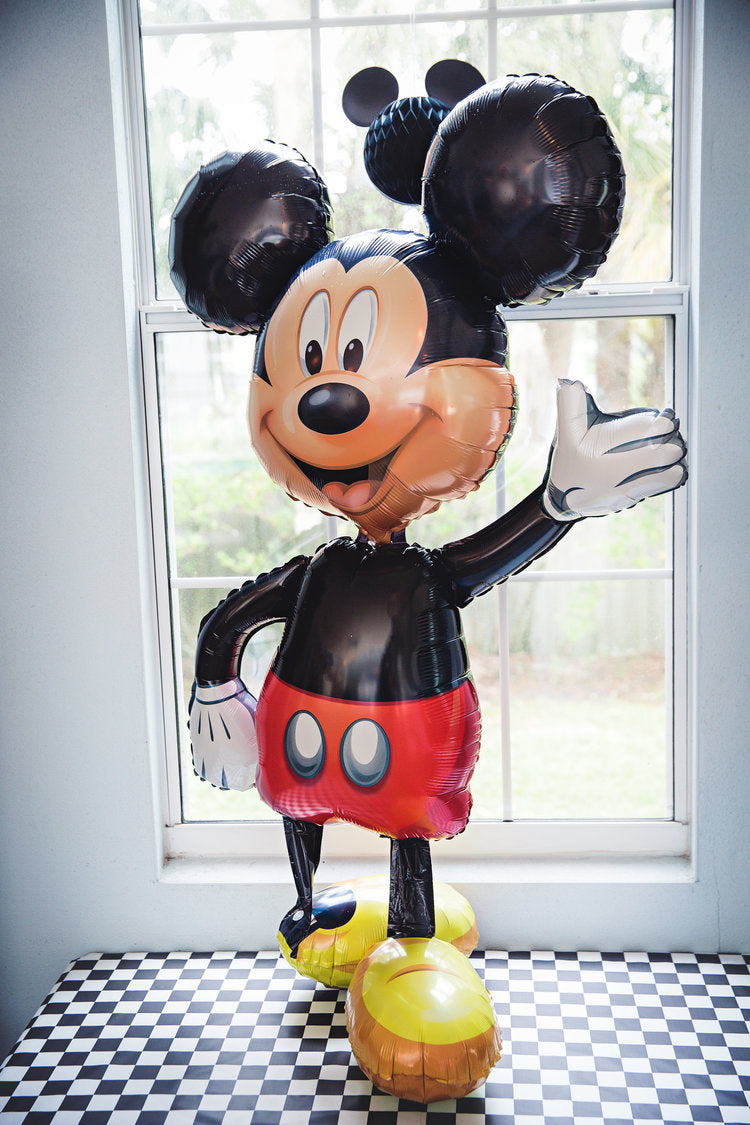 Mickey Mouse mylar balloon standing on black & white checkerboard table