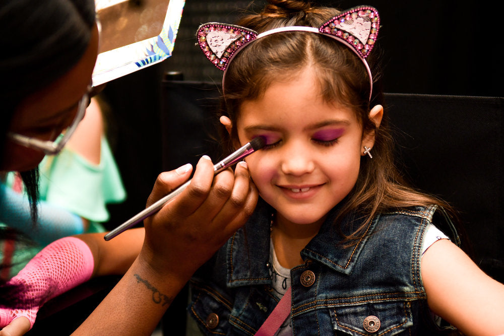 Makeup artist giving makeover to birthday party attendee