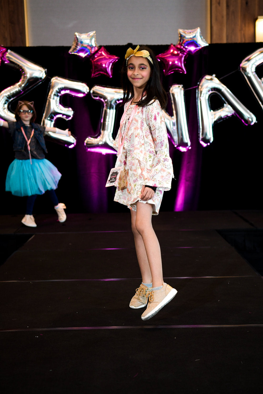 Birthday party attendee posing on runway for birthday fashion show
