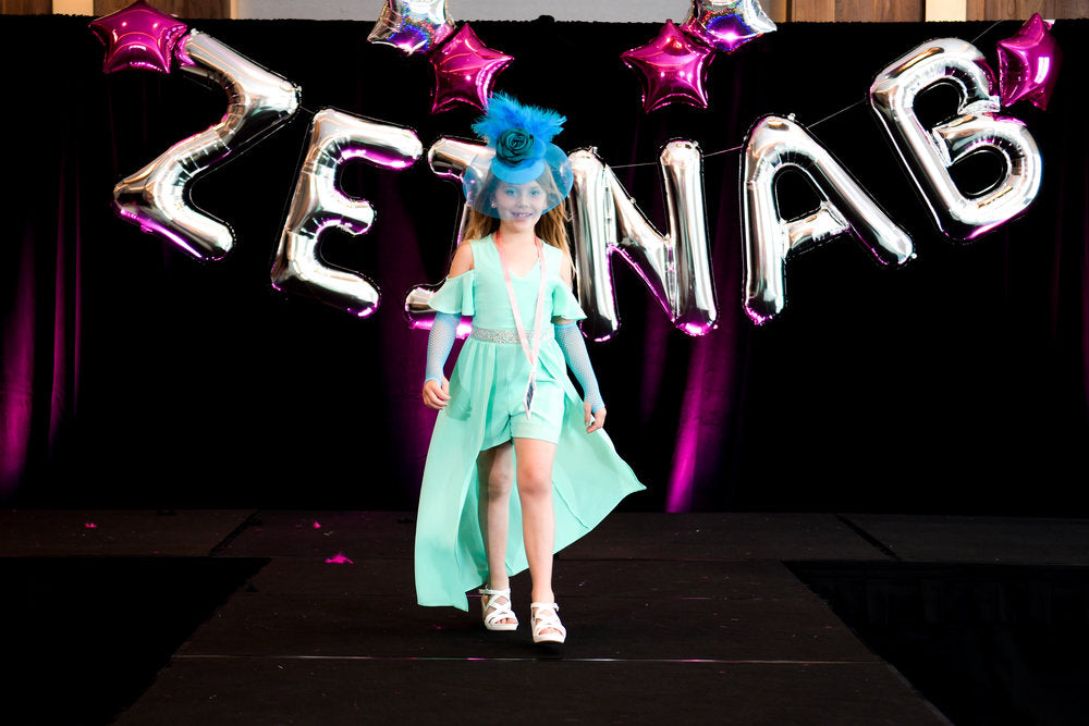 A birthday party attendee walking down runway for birthday fashion show