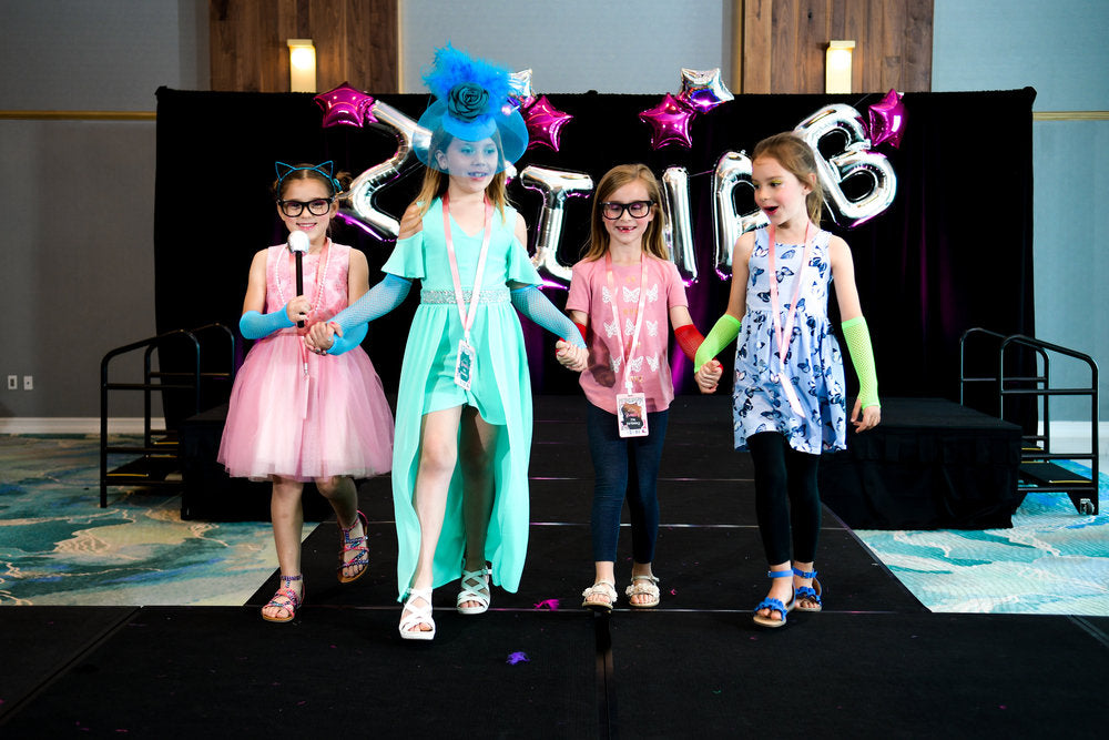 4 birthday party attendees walking down runway for birthday fashion show