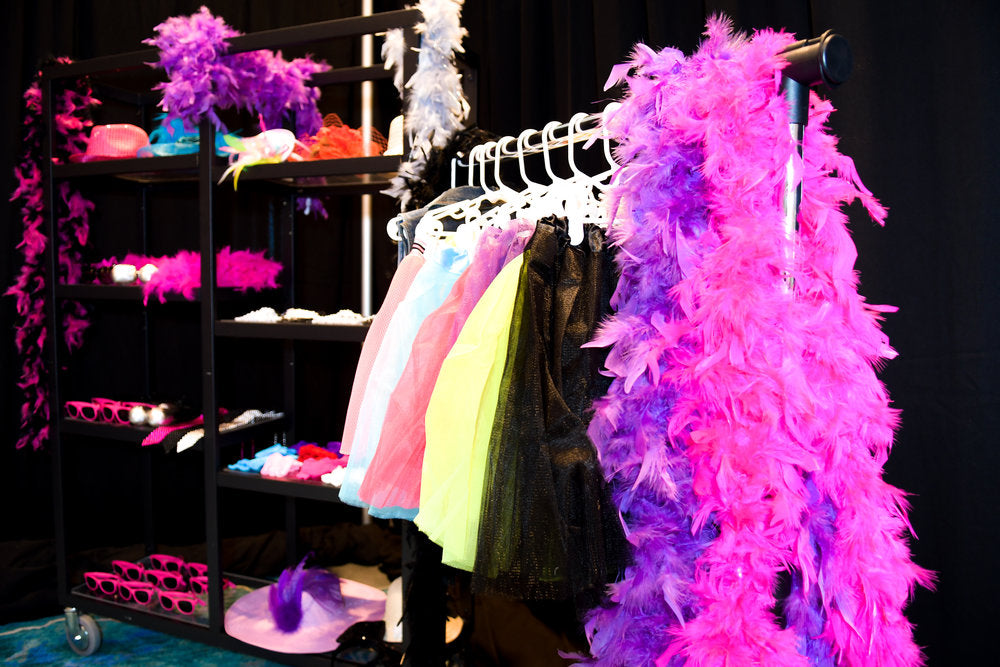 Dress up area with sunglasses, hats, skirts, and feather boas