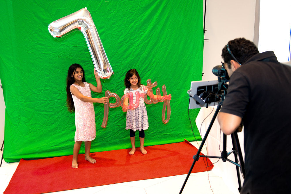 2 girls holding balloons standing in front of green screen as photographer takes their photo