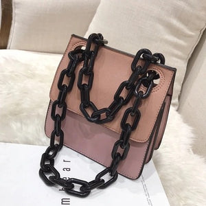 pink monotoned bag with black chain straps handle edgability top view