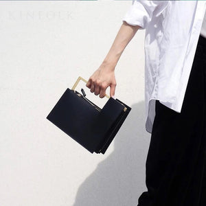 classy black bag formal clutch bag with gold handle edgability front view