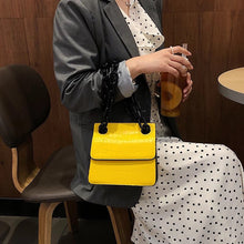 croc skin yellow sling bag with black strap edgability model view