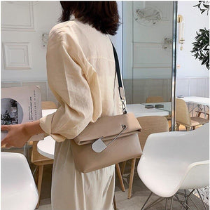 beige clutch bag with safety pin edgability model view