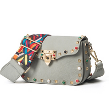 multi coloured studded sling bag angle view edgability
