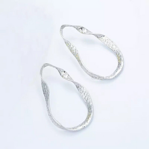 curved silver earrings silver jewelry edgability top view