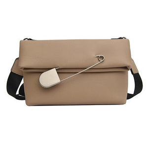 beige clutch bag with safety pin edgability
