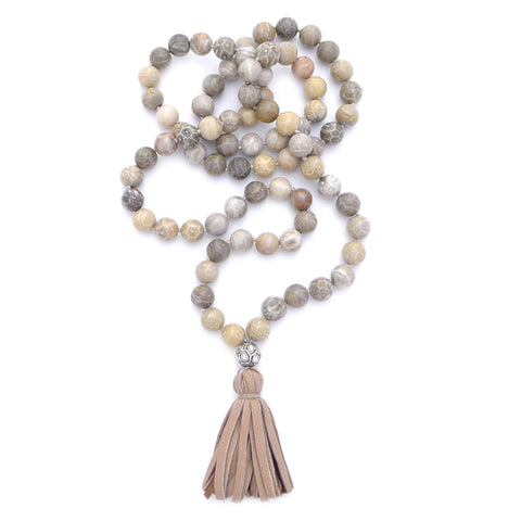 knotted fossilized coral with diamond ball & tassel