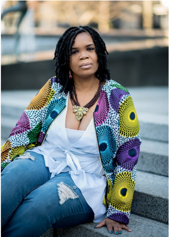 Founder of Brown Girls Collective, Marcie Thomas, is featured sitting on cement steps with white shirt and tribal blazer