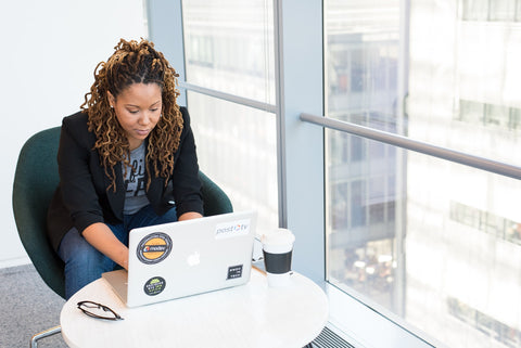Black woman with locs looks at computer in business setting