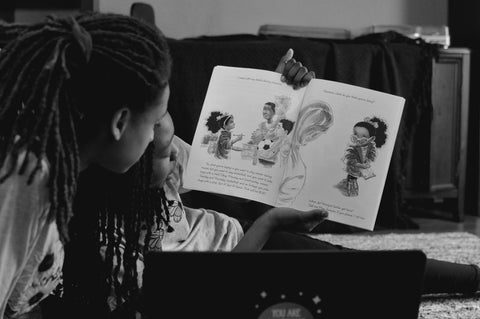 Black child with locs reading a book with Black adult with locs