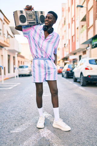 Black man wearing pink and blue romper smiling and holding a large radio (Boom Box)