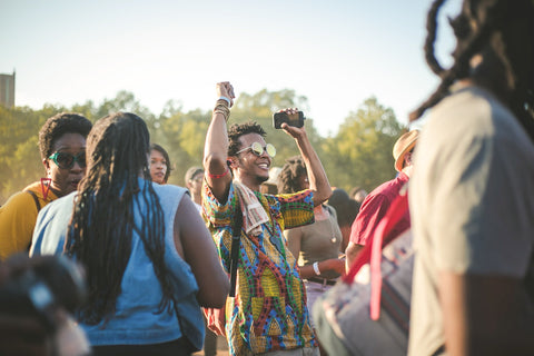 Black person smiles and dances in outdoor festival setting