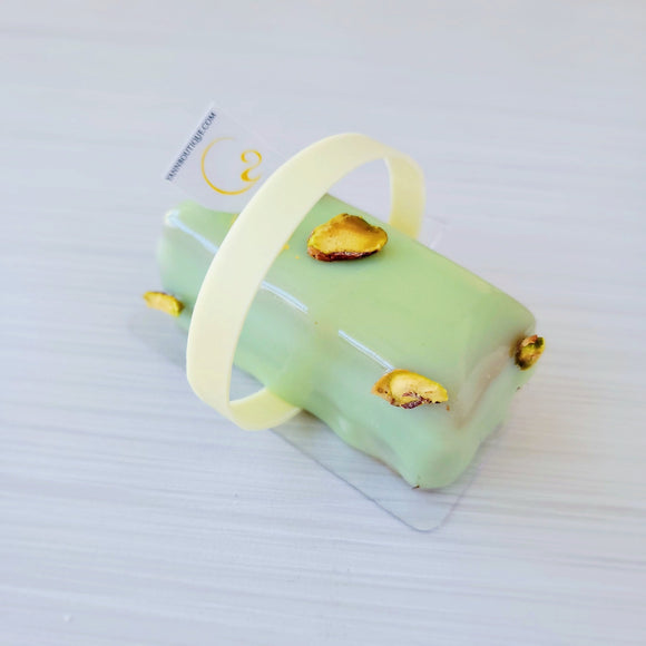 Enjoy layers of pistachio praline, yuzu marmalade, orange blossom pistachio & almond cake with a pistachio ganache!
