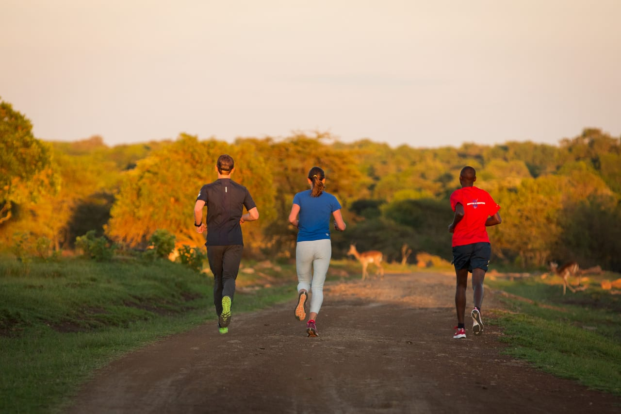 Tourists running with a Kenyan athlete