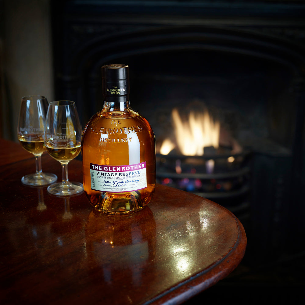 Single bottle of Peated Reserve & Glasses Placed on a Table with open fire in background