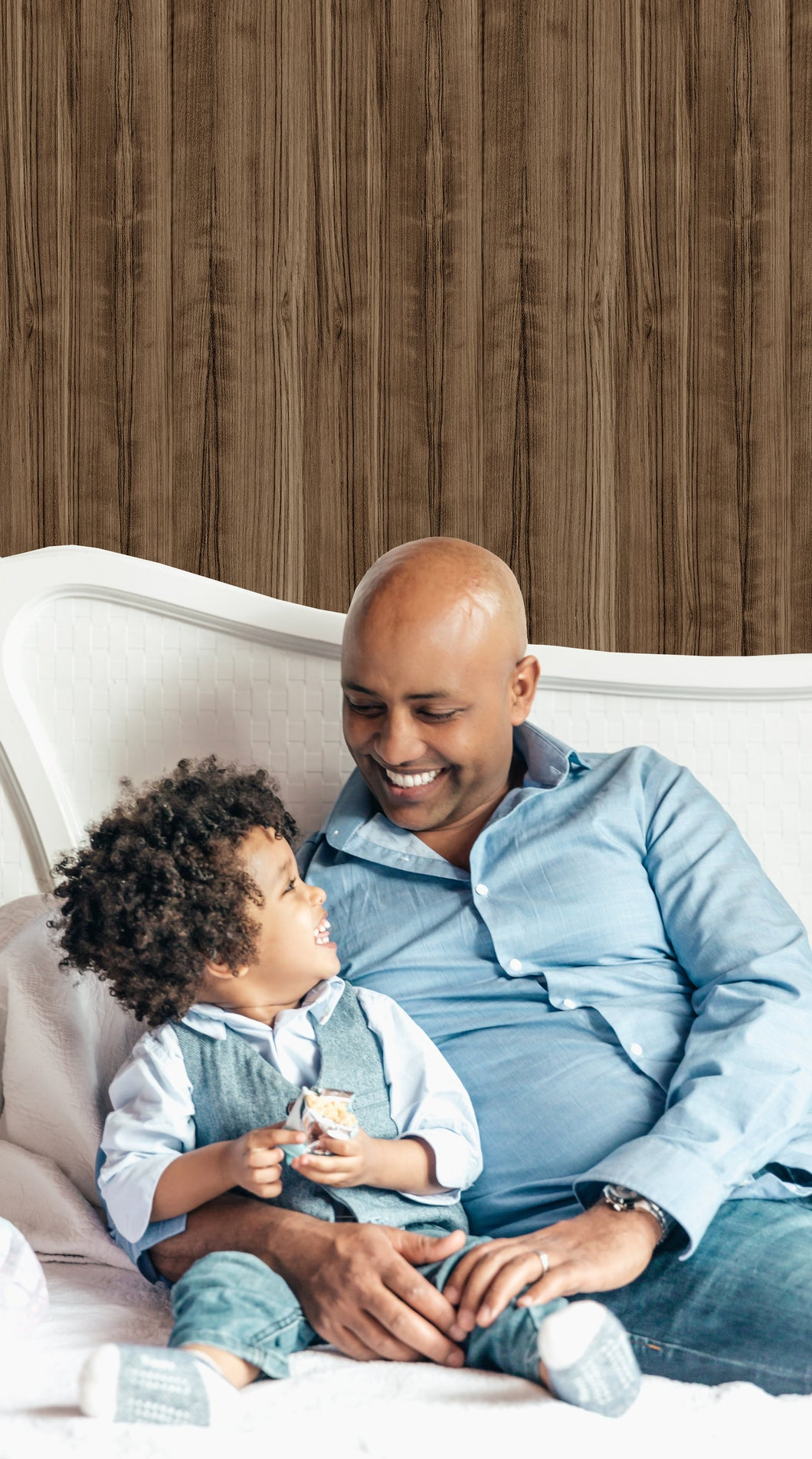 happy dad with child. sitting in front of wood grain wallpaper.