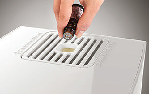 Close-up of top of Boneco S250 humidifier showing a hand pouring essential oil in to add a scent