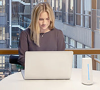 a woman seated at a desk working on a laptop with a Blueair Aware device in foreground