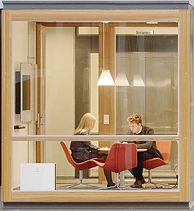 Blueair Pro M shown situated in a high-ceilinged, glass-walled shared office where two people are working