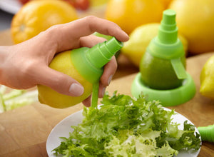 Spraying fresh lemon juice onto a salad with a Lekue Silicone Citrus Spray Extractor
