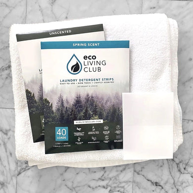 two packages and strips of Eco Laundry Detergent Strips on folded towels