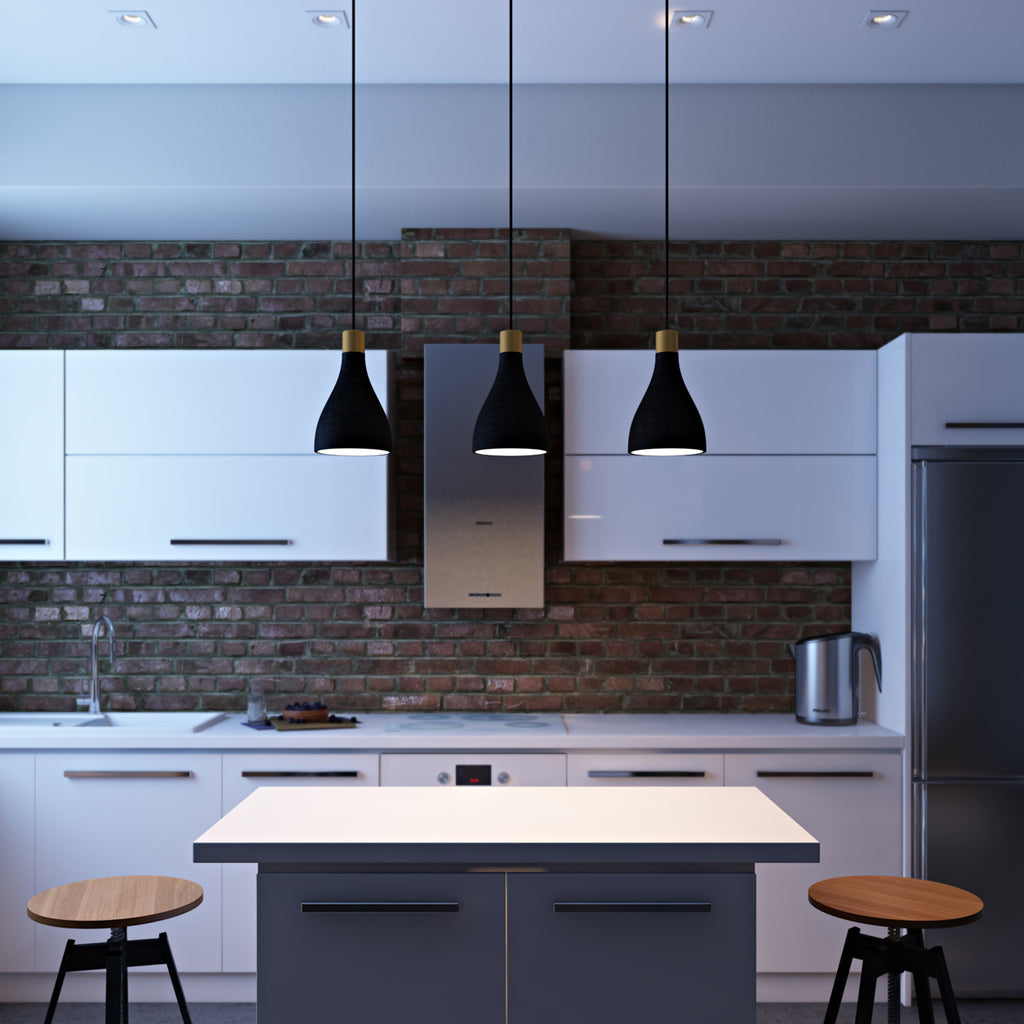 Three charcoal La Brea LED pendant lights hanging over a high top counter in a brick kitchen with white cabinets