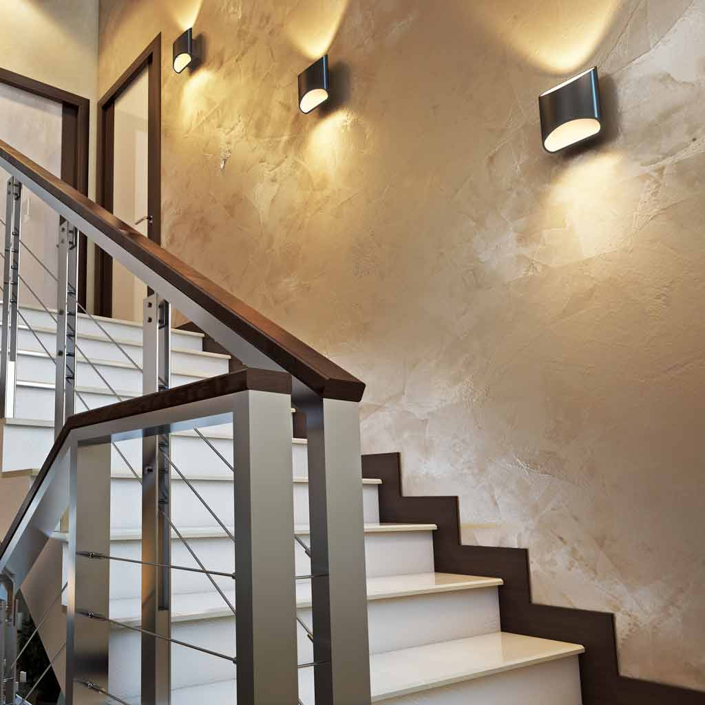 Three black slate Brooklyn LED wall sconces mounted in the stair case of a home
