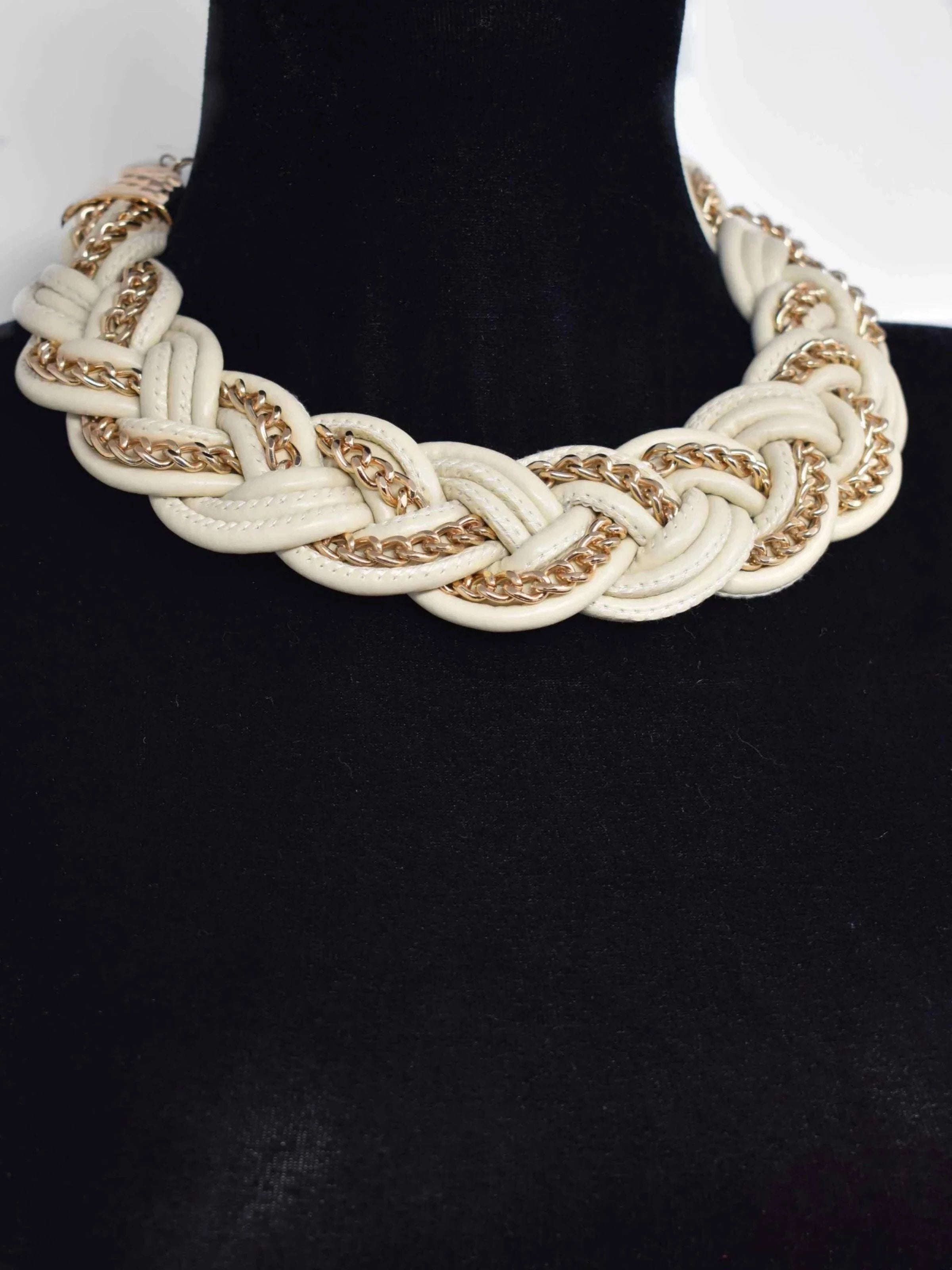 "Get all the attention in the Agera statement necklace. This cream braided necklace is accented with gold chain trimming for a unique design. It messures 18"" in length and has a lobster clasp."