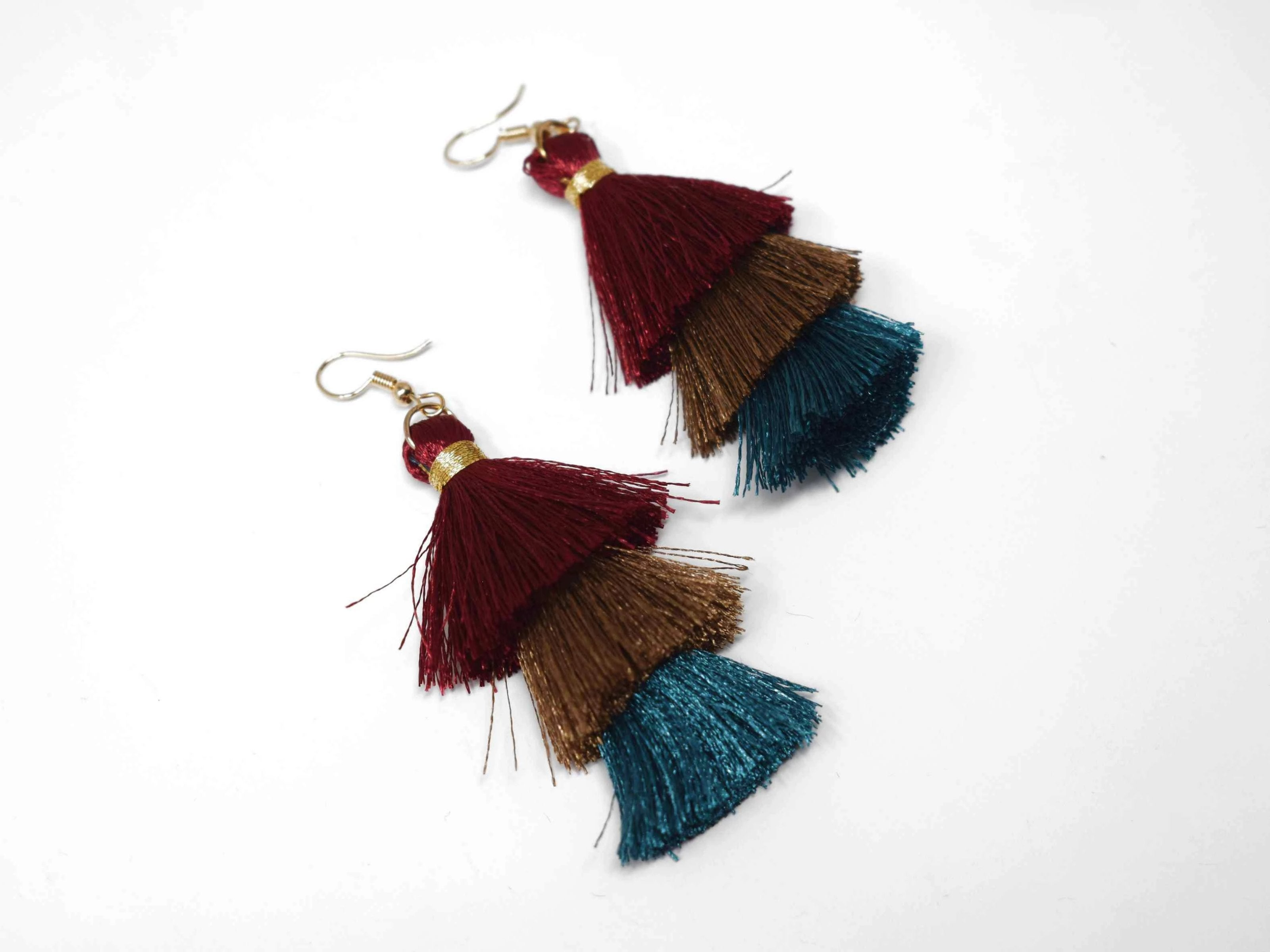 "You can count on our Allium earrings to provide you with a little fringe with benefits.  These triple layered burgundy, brown and green fringe earrings are a beautiful addition with there fish hook clasp. They measure 3 1/2"" in length."
