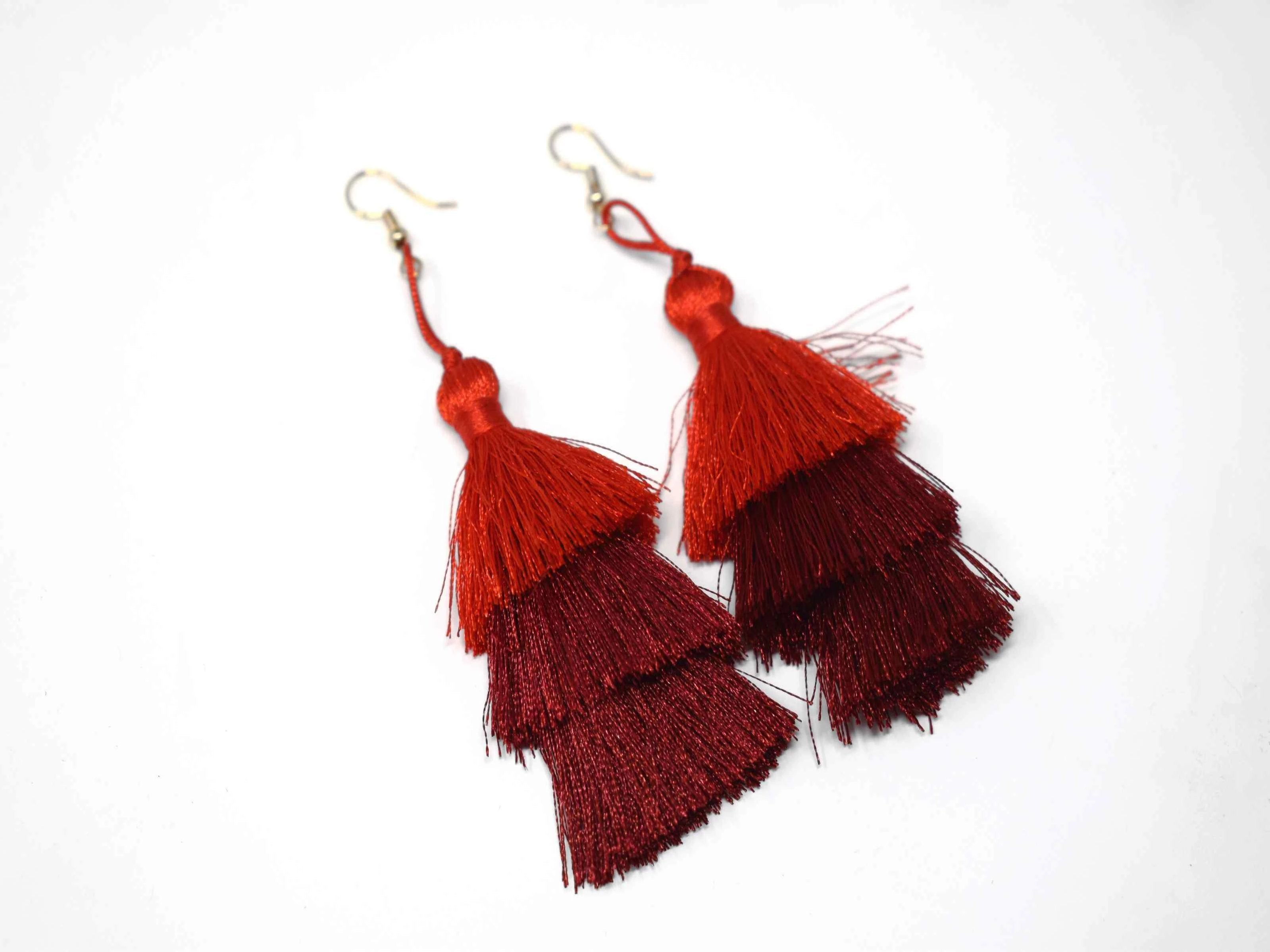 "You can count on our Allium earrings to provide you with a little fringe with benefits.  These triple layered red and burgundy earrings are a beautiful addition with there fish hook clasp. They measure 3 1/2"" in length."