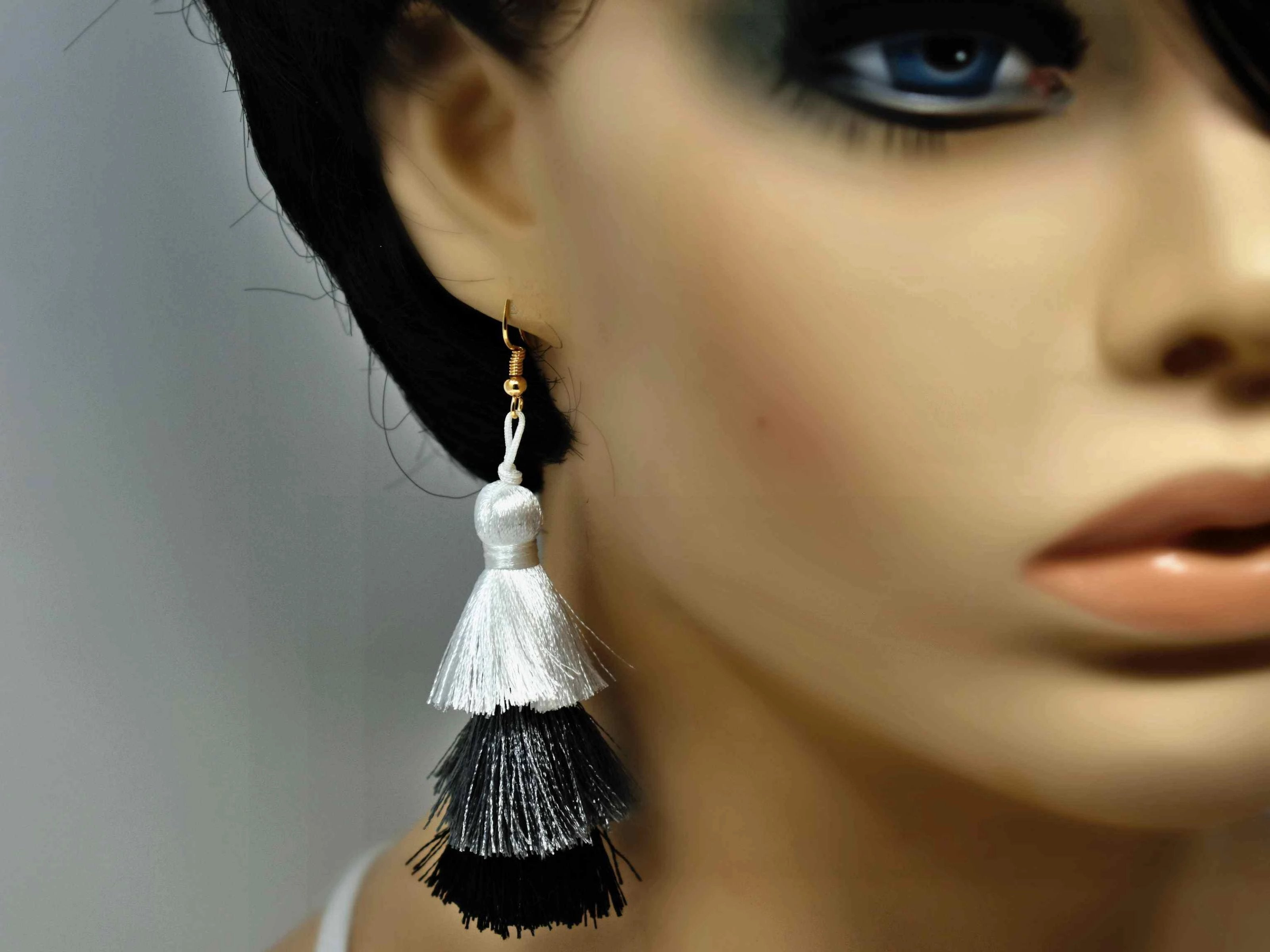 "You can count on our Allium earrings to provide you with a little fringe with benefits.  These triple layered white grey and black earrings are a beautiful addition with there fish hook clasp. They measure 3 1/2"" in length."