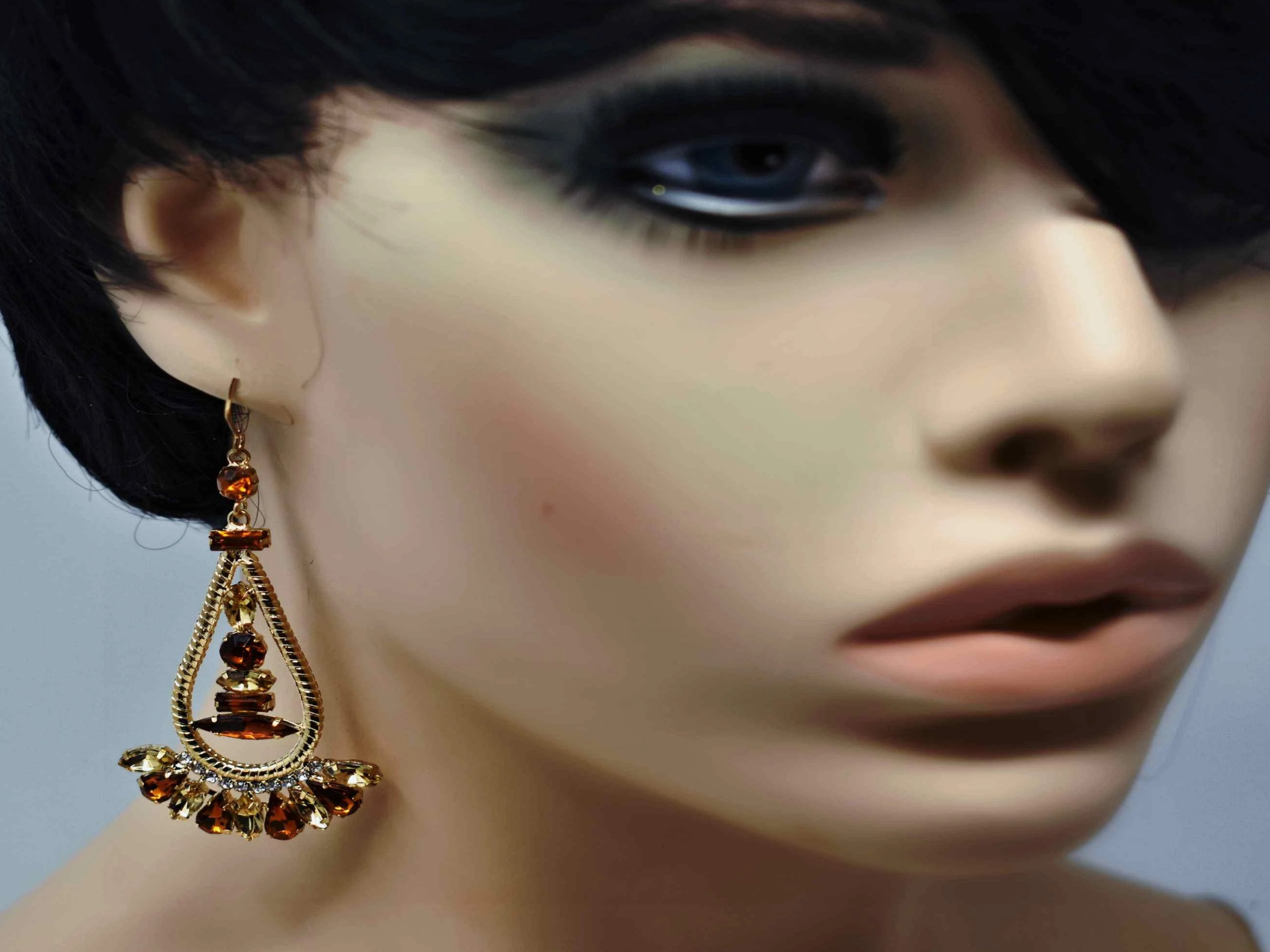 Anemone is a gold with bronze stone eye catching drop , dangle style earring. It comes with a fish hook clasp and is 3 inches in length.