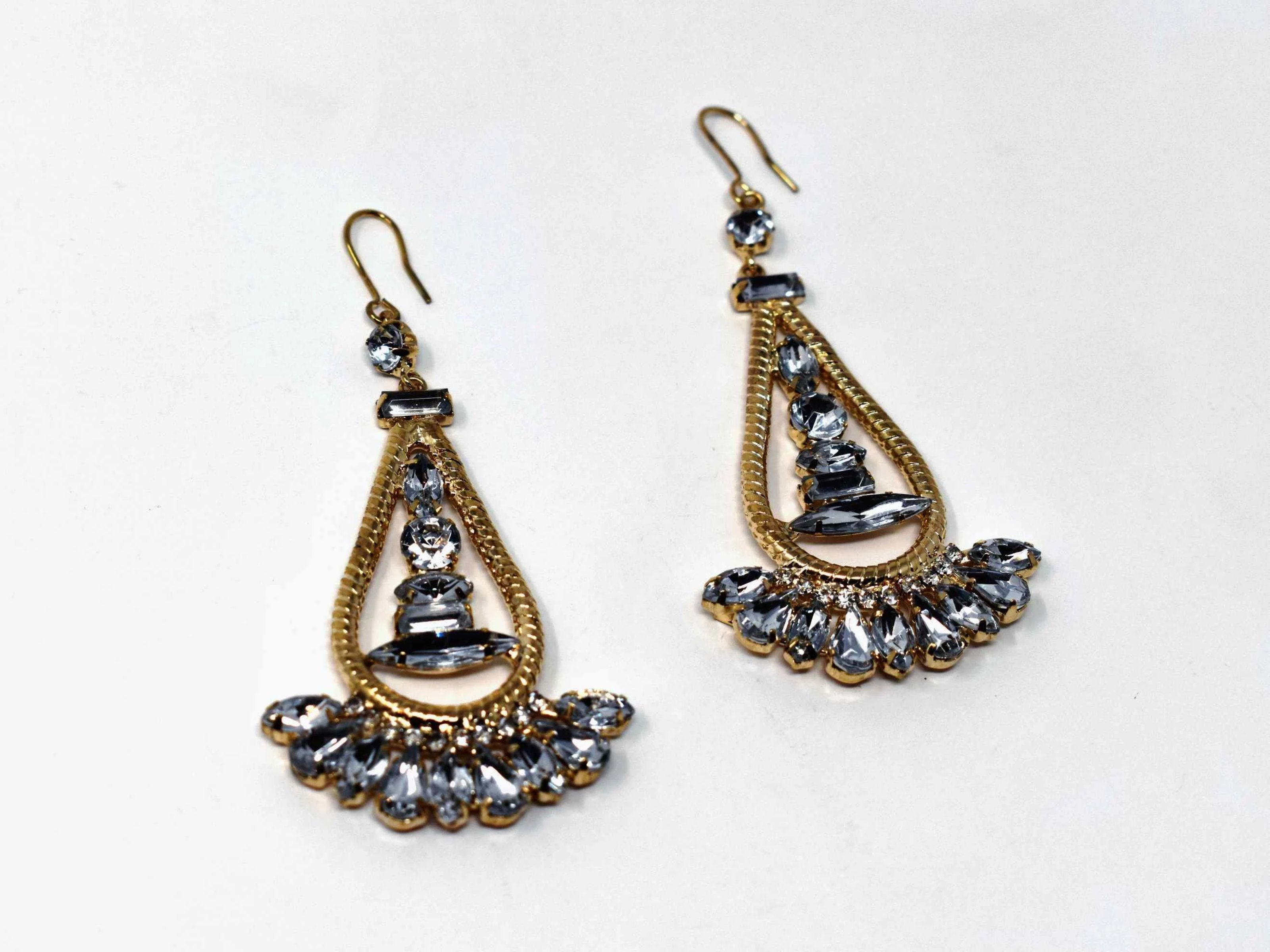 Anemone is a gold with clear stone eye catching drop , dangle style earring. It comes with a fish hook clasp and is 3 inches in length.