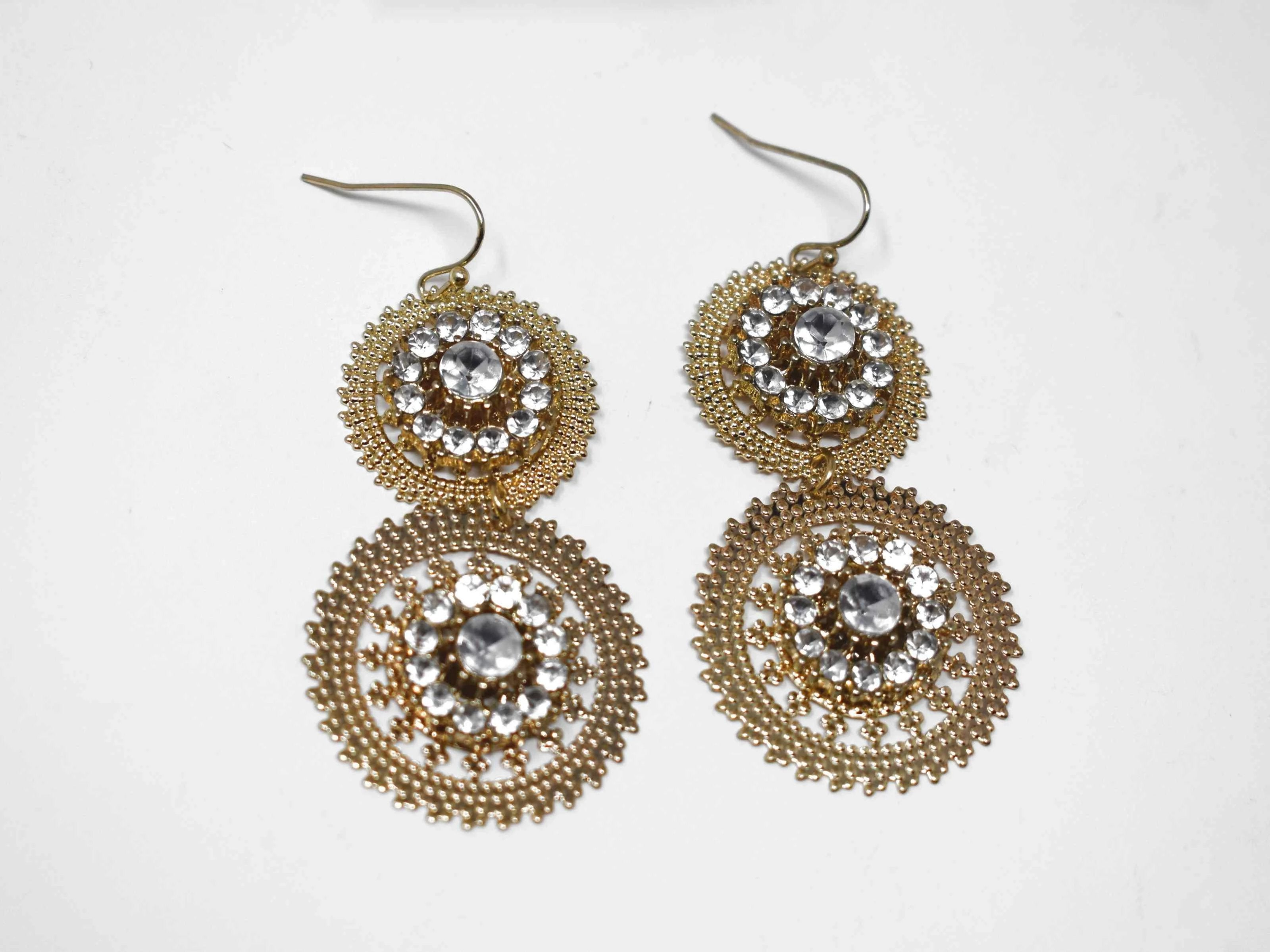 "Our Aster is a chic gold tone drop dangle style earring accented with clear stones. It measures around 2 1/2"" in length."