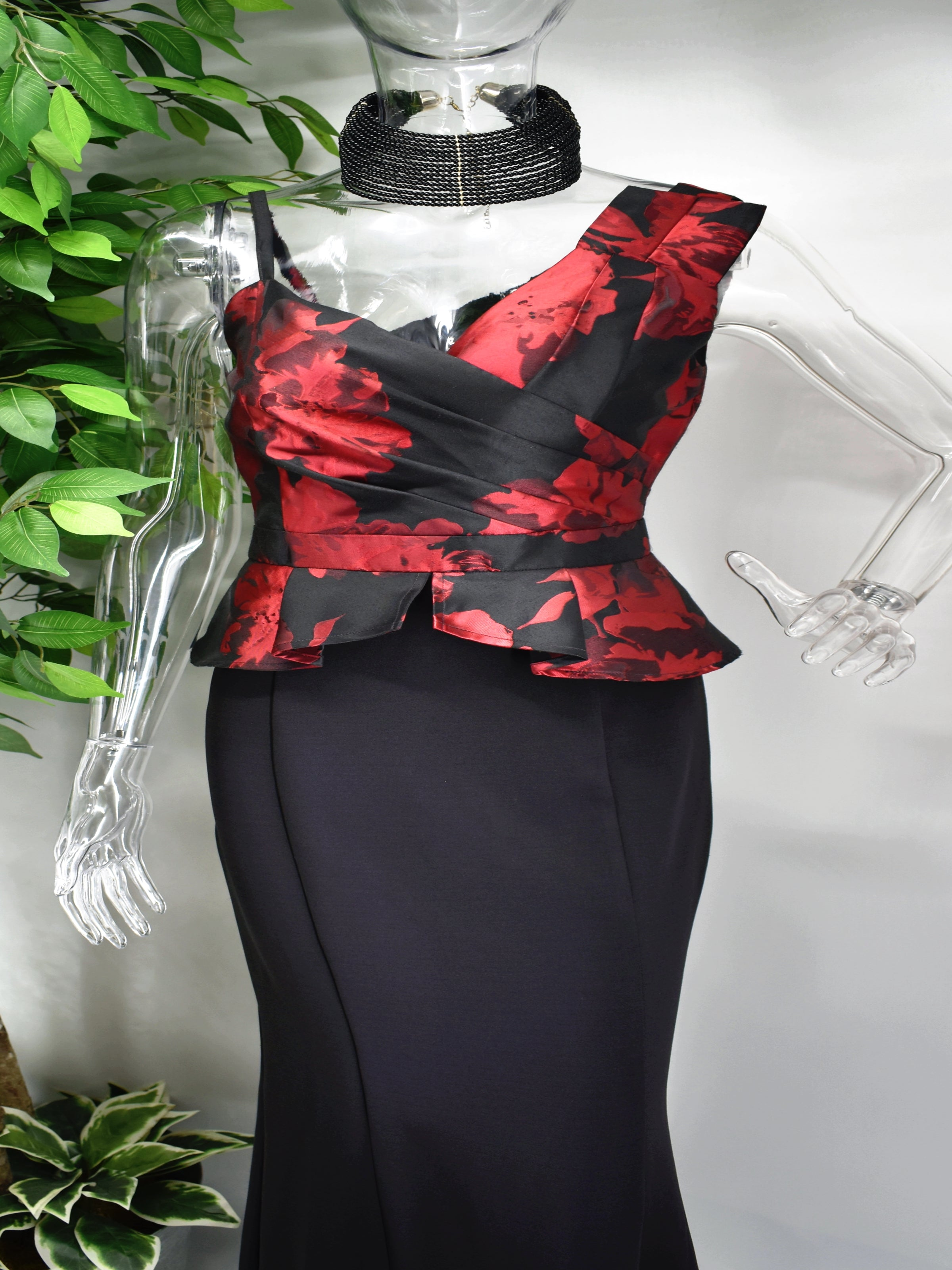 Be anything but basic in our stunning Baleigh long formal dress.  Baleigh has an asymmetrical sweetheart neckline paired with a fitted peplum bodice. The Bodice is adorned with red floral detailing and flows into a long black fitted skirt.