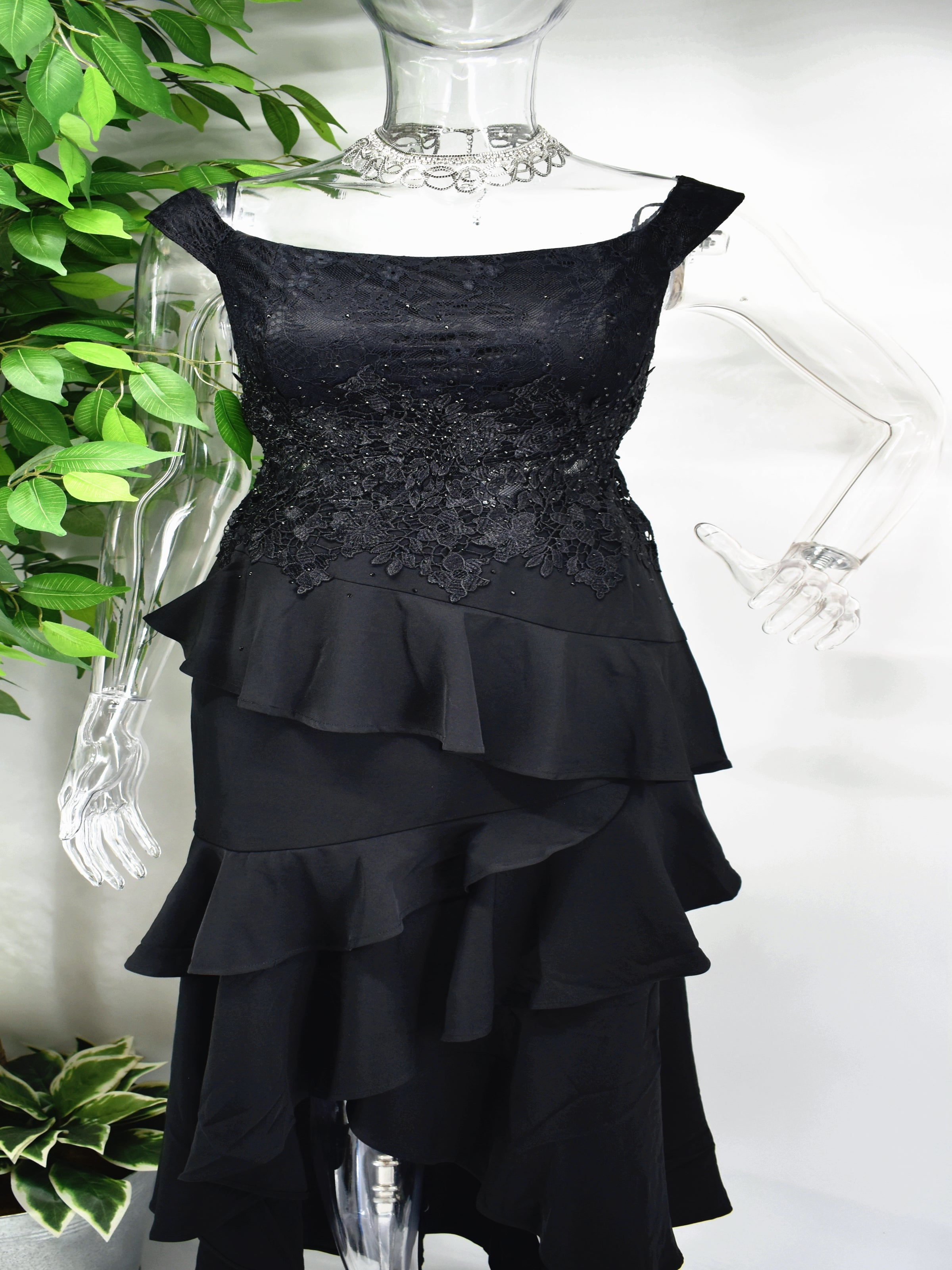 There is so much to love about our incredible Bedelia Black dress. The black formal dress has a boat neckline accompanied by a beaded bodice and frills cascading down to the hem of the dress.