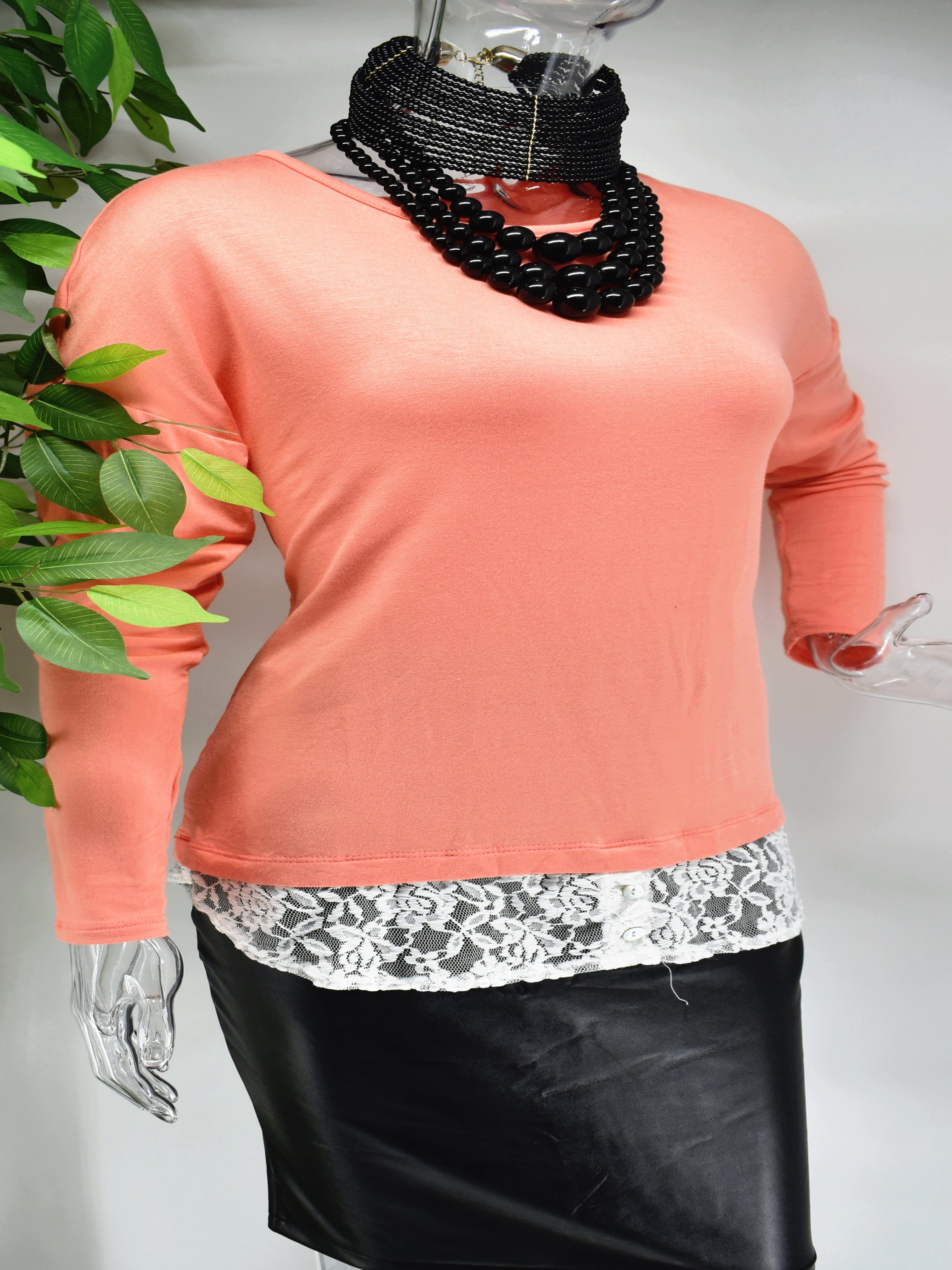 Influence the outcome today in our Belina top. Our Belina is a soft knit peach colored top with lace at the base of the of the top.