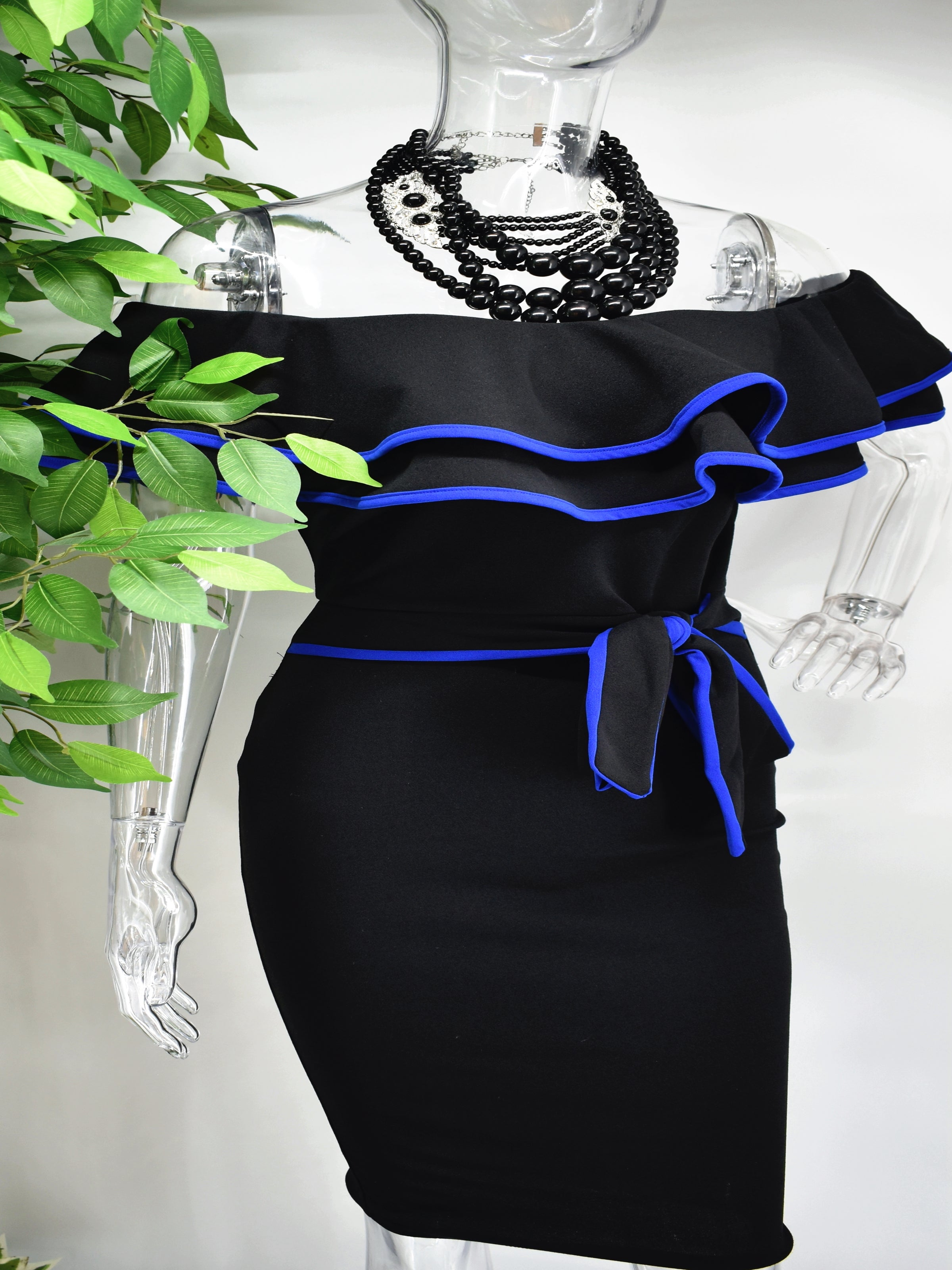 Our Berdine Black Midi Dress is picture perfect with its off the shoulder ruffled neckline and fitted bodice. The ruffled neckline and belted waist is piped with a beautiful blue.