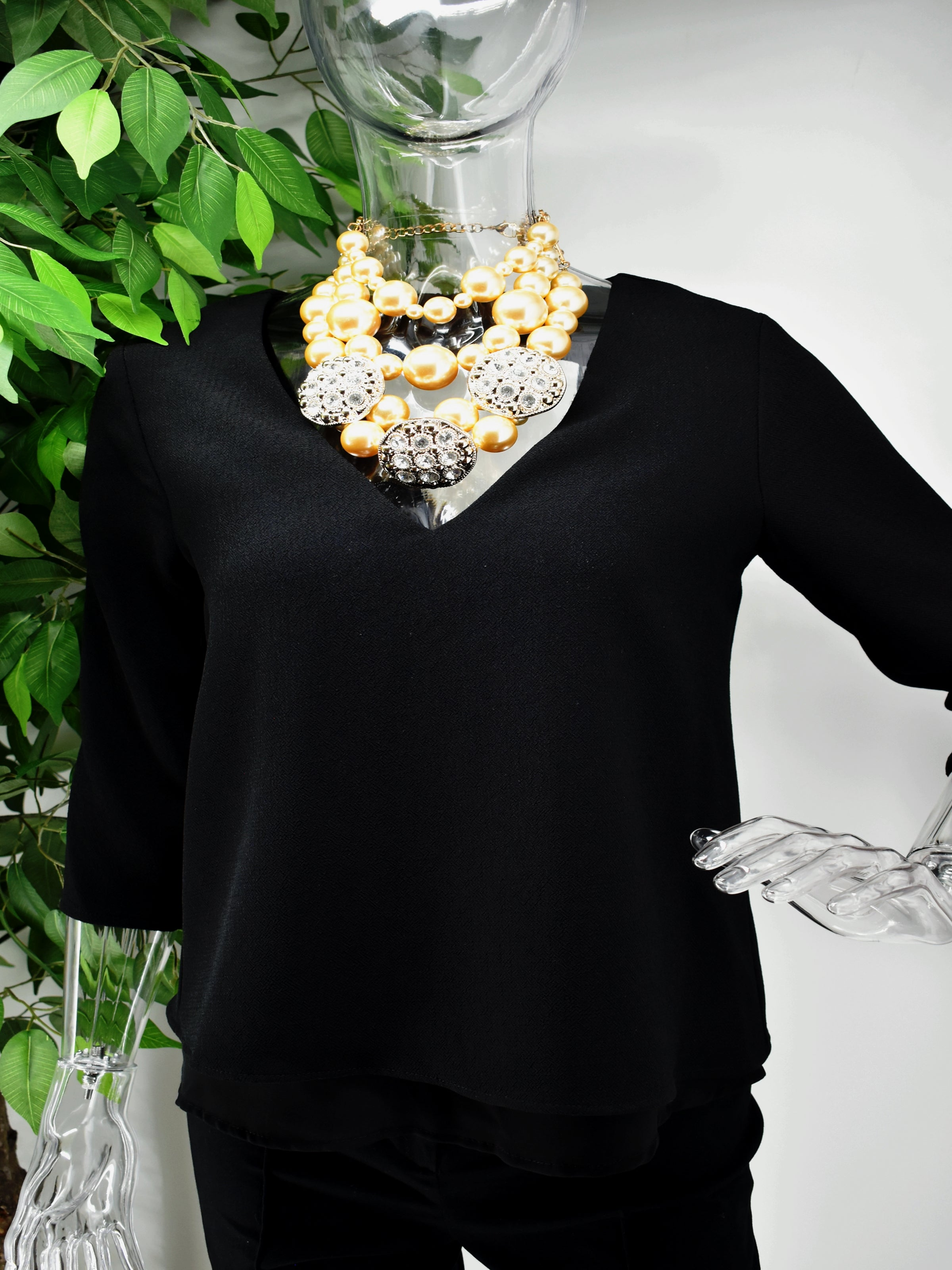 You can do no wrong in our Bernessa Blouse. Bernessa is a black v neck blouse with an accent gold zip to the back of the blouse.