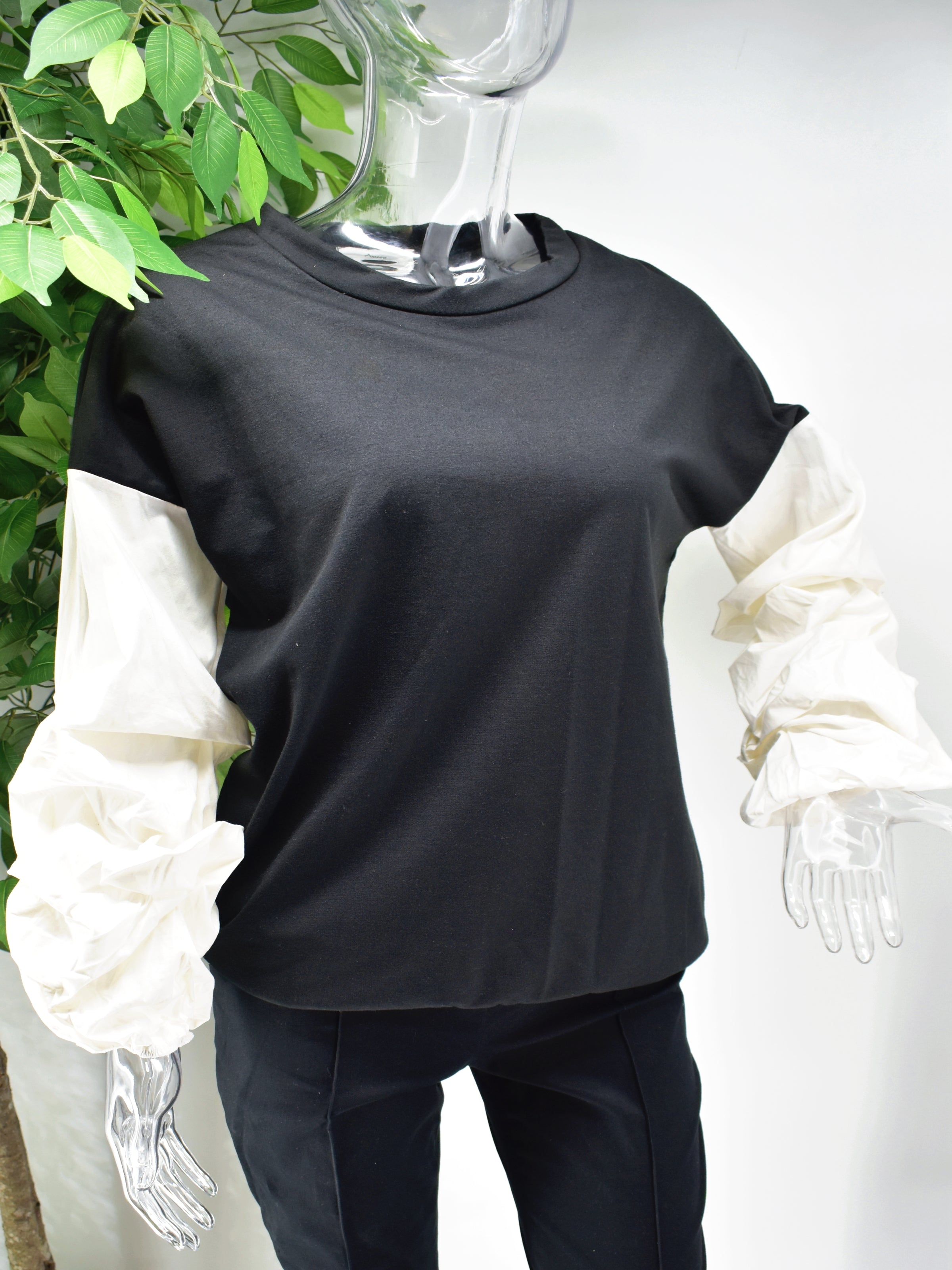Let's Reinvent the sweater with our Bianey Black sweater top.  Our Bianey top is a black sweater top with a white puffed rouged sleeve.