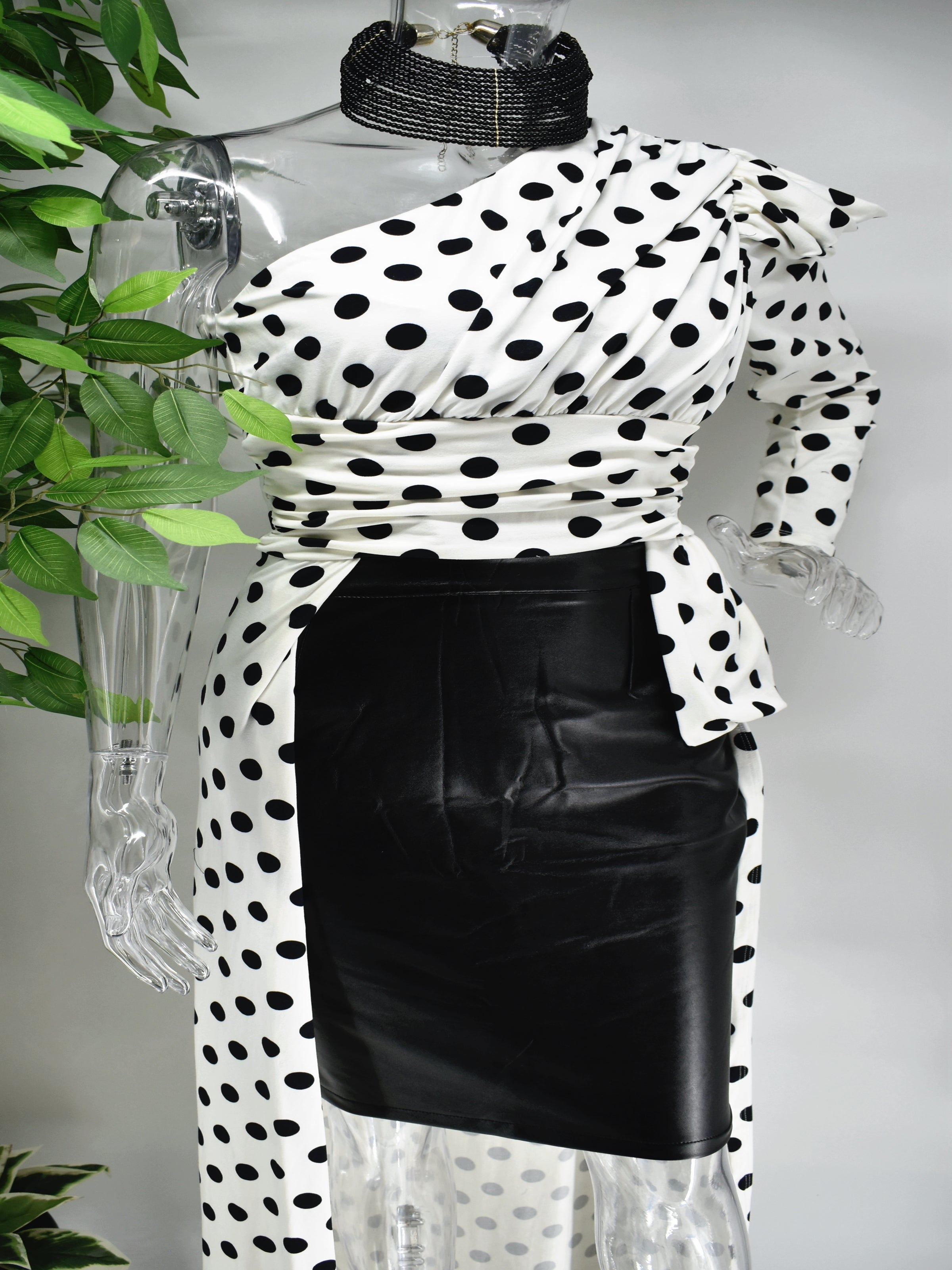 Let's go out and get Jiggy in our Biddy white with black polka dot top. Biddy's unique one sleeved asymmetrical design is complimented with a short and long hem. This top would be great paired with skirts, pants leggings or shorts.