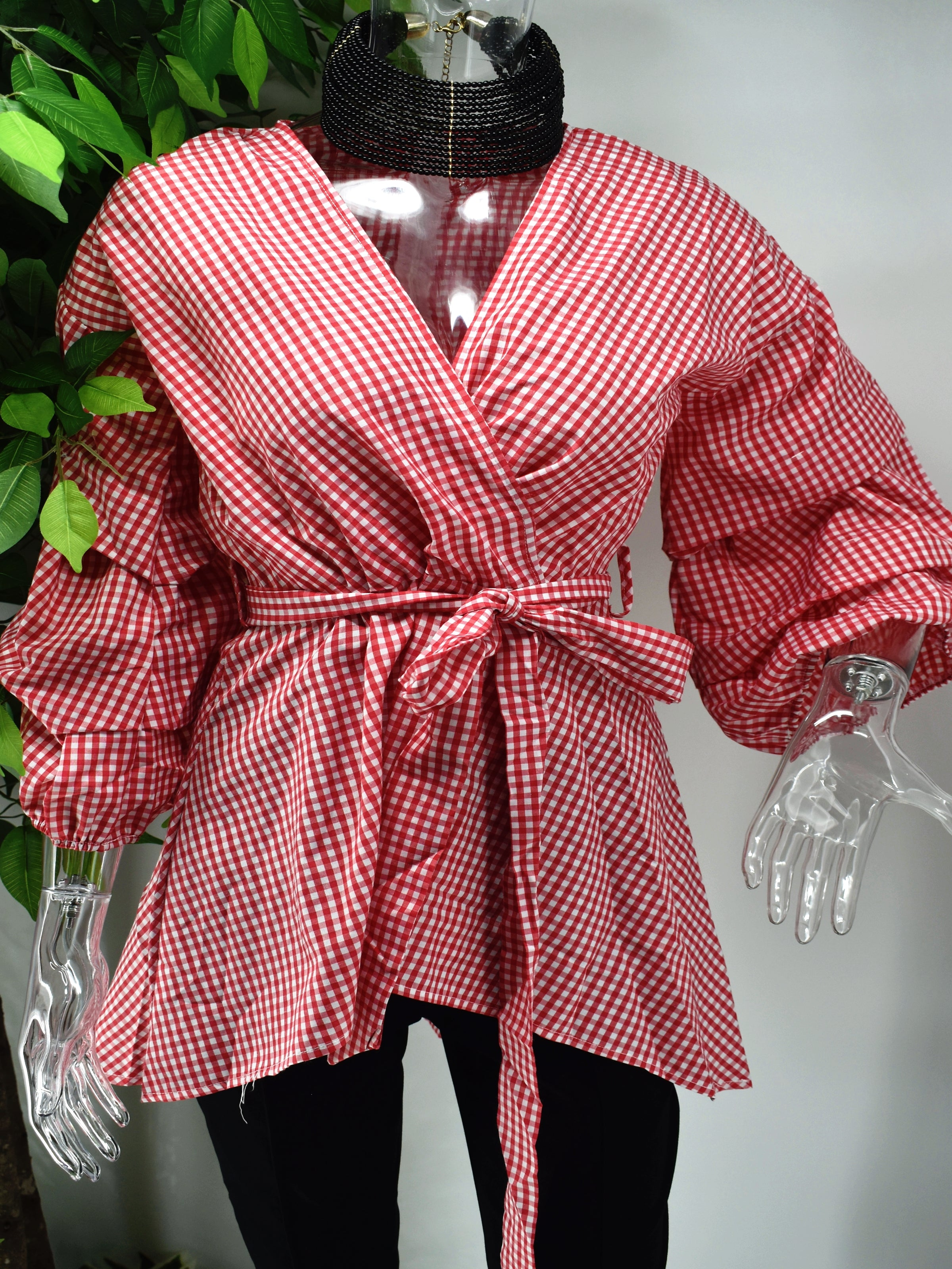 A classic print meets a modern design with our Birdina red and white gingham print top. Our Birdina is full of style and pizzaz. It has a v-neckline, ruffled puffed sleeve and an uneven hem. The design is completed with a tied cinched waist.