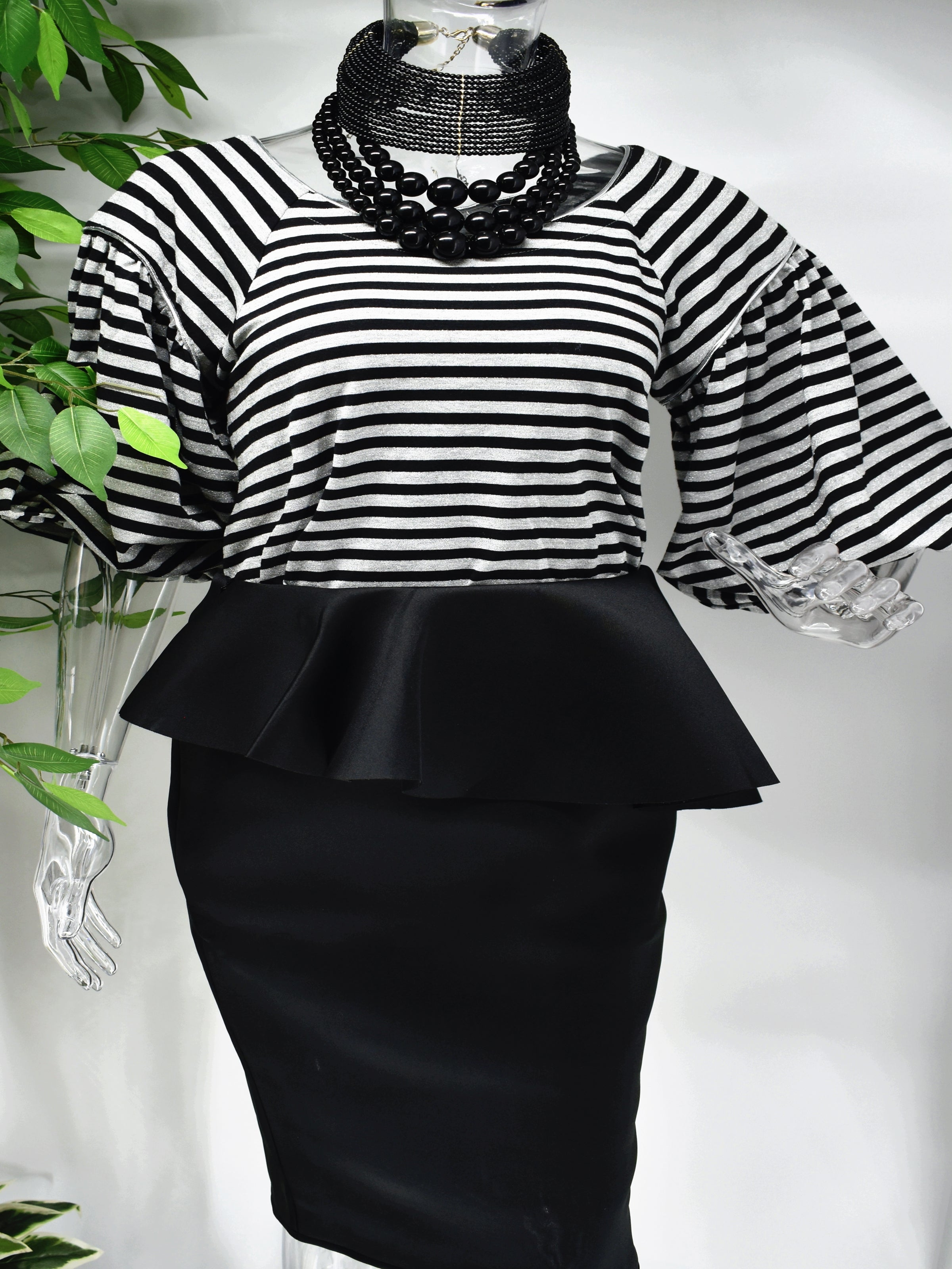 Bring a modern design to a classic staple when you step out in our Bobette stripe top. Bobette has a black and gray striped design with a bateau neckline that is beautifully paired with our high fashion puffed bell sleeve.